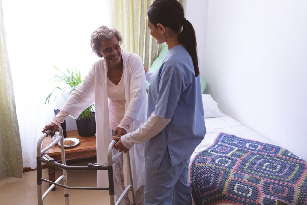 female nurse helping senior female patient